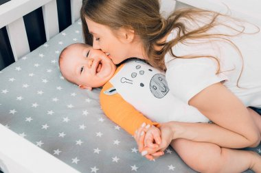Happy family, Mother and child on a white bed. Mom and baby boy are playing. A parent and a small child are resting at home. Family has fun together