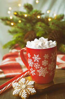 Close-up of a mug with a hot drink, marshmallow and gingerbread. Christmas decor with a bright garland and fir tree. Selective focus, shallow depth of field, background