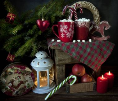 Close-up of red mugs with hot drink and marshmallow. Christmas decor with fir tree on background