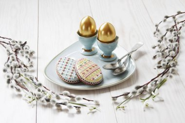 close-up photo of Easter golden eggs on plate with cookies and metal spoons on wooden background with willows branches