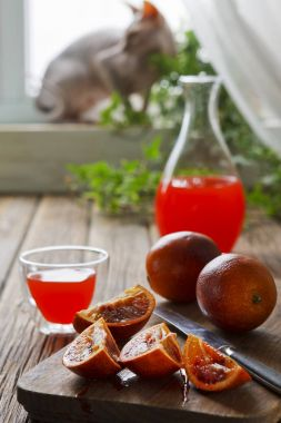 Close-up of sliced blood orange on wooden board,  glass of orange juice and  glass jug against the window with silhouette of sphinx cat. Selective focus, shallow depth of field on a vintage wooden background