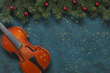 Old violin and fir-tree branches with Christmas decor wits glitt