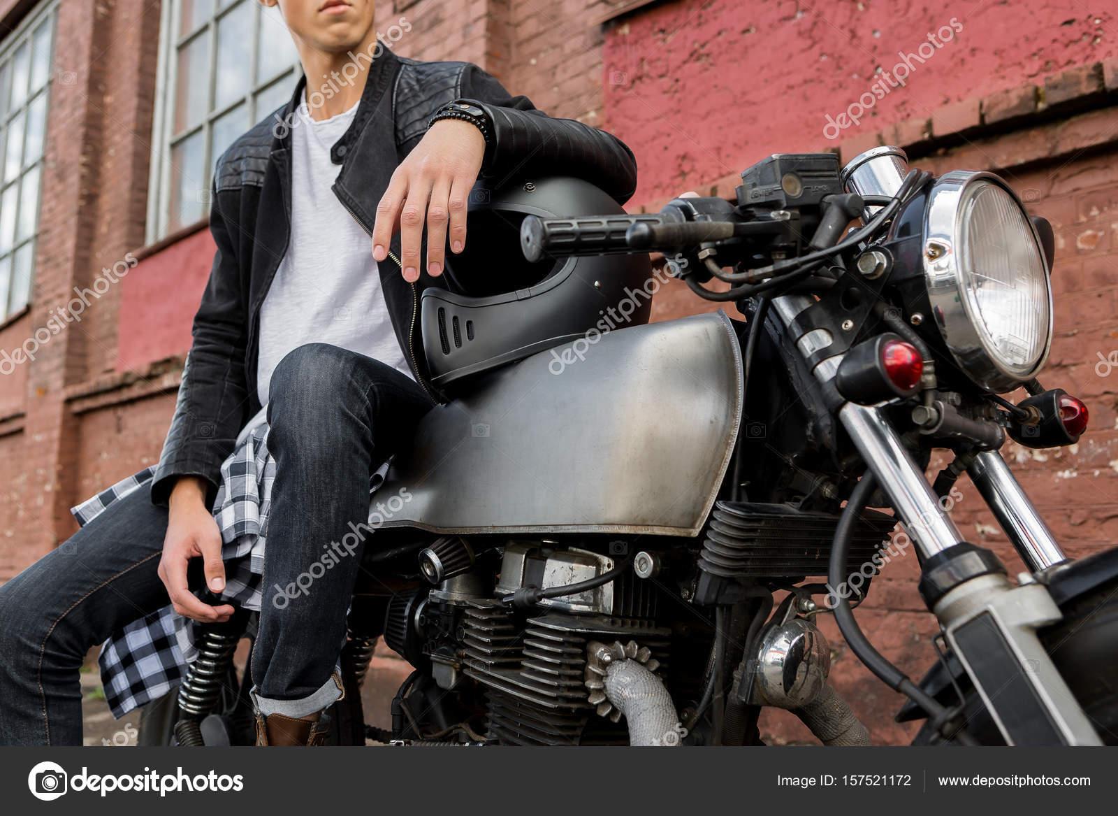 Close Up Of A Handsome Rider Biker Guy Hand In Black Leather Jacket On Helmet Classic Style Cafe Racer Motorcycle Bike Custom Made Vintage Garage