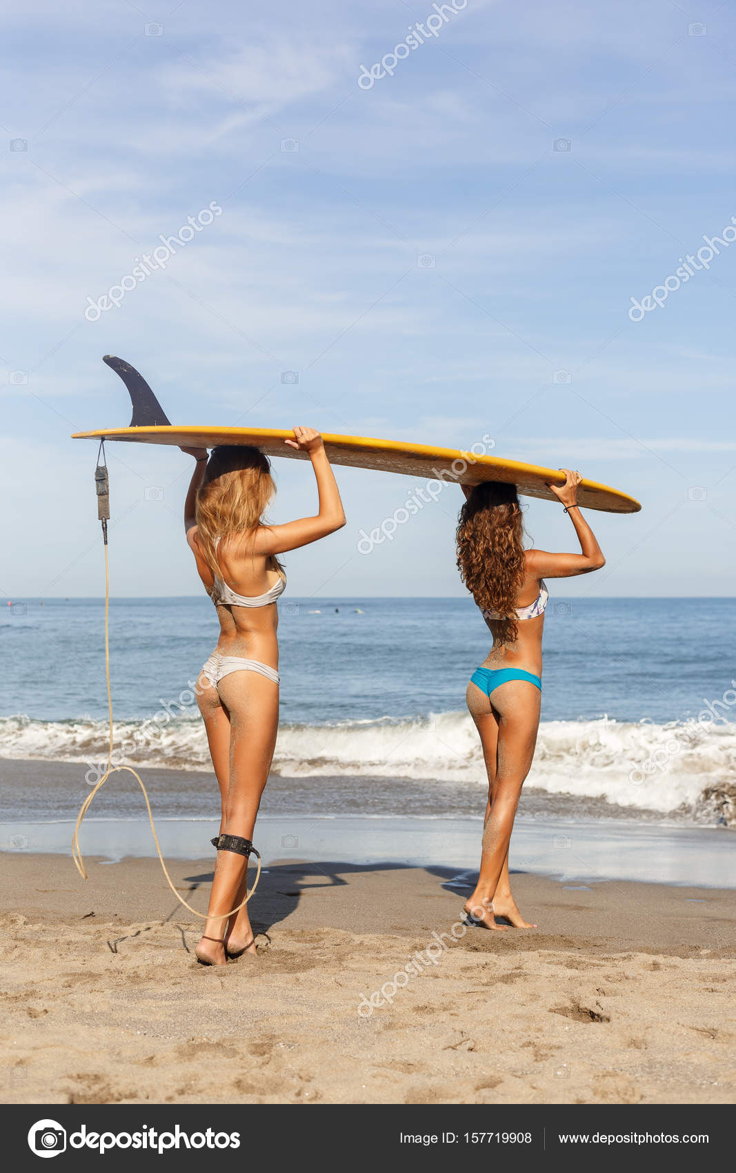 Two Beautiful Surfer Girls At The Beach Go Into The Water