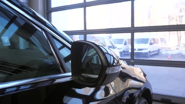 Nové černé auto v prodejně aut. Prvky toho auta. Denní světlo