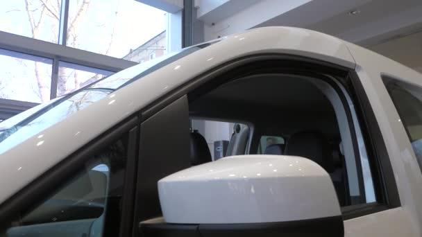 Nové bílé auto v prodejně aut. Prvky toho auta. Denní světlo