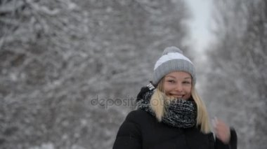 A young girl acts outdoors in the winter,beautiful girl laughing on the background of winter trees in the snow