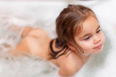 Little pretty girl is taking a bath with a foam