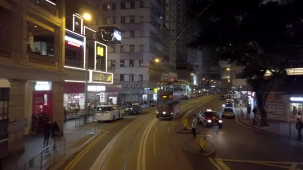 Hong Kong, China - 2020: Double-decker trams ride down the street at night