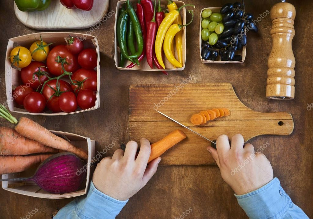 Man cooking and slicing fresh vegetables on a rustic kitchen wor
