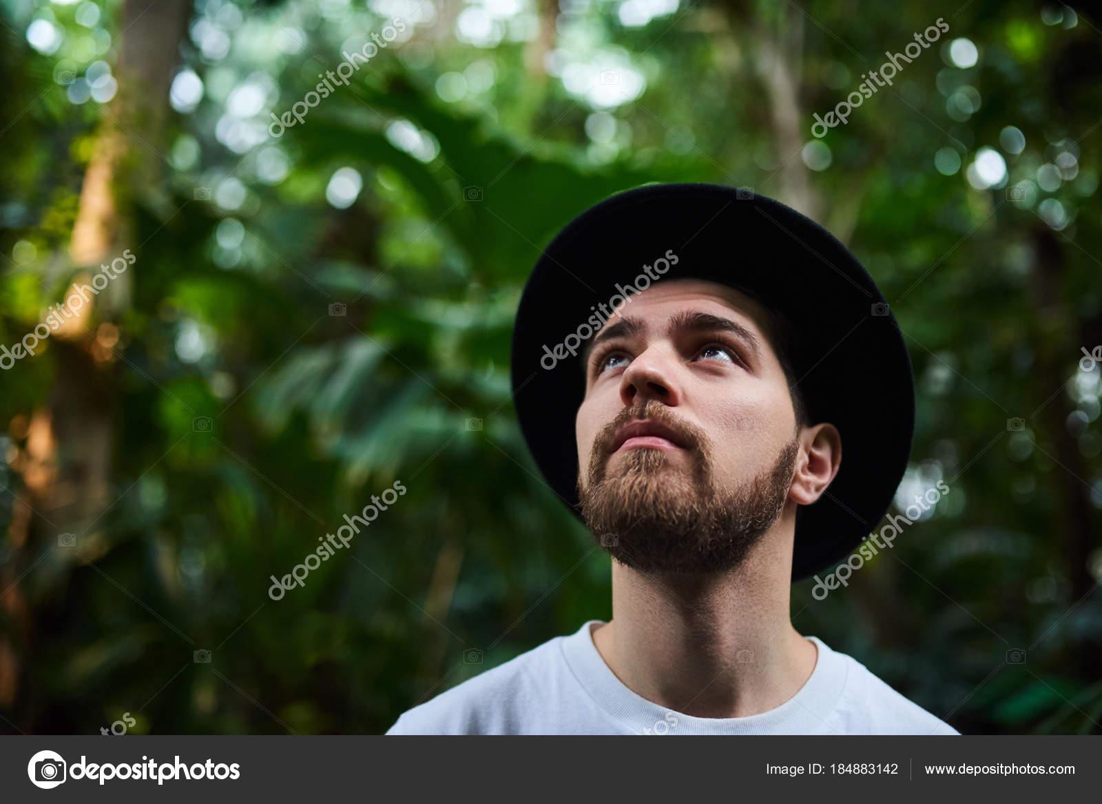 Closeup retrato de guapo elegante barba hombre con pie de sombrero negro en  el jardín botánico 31d9cf64033