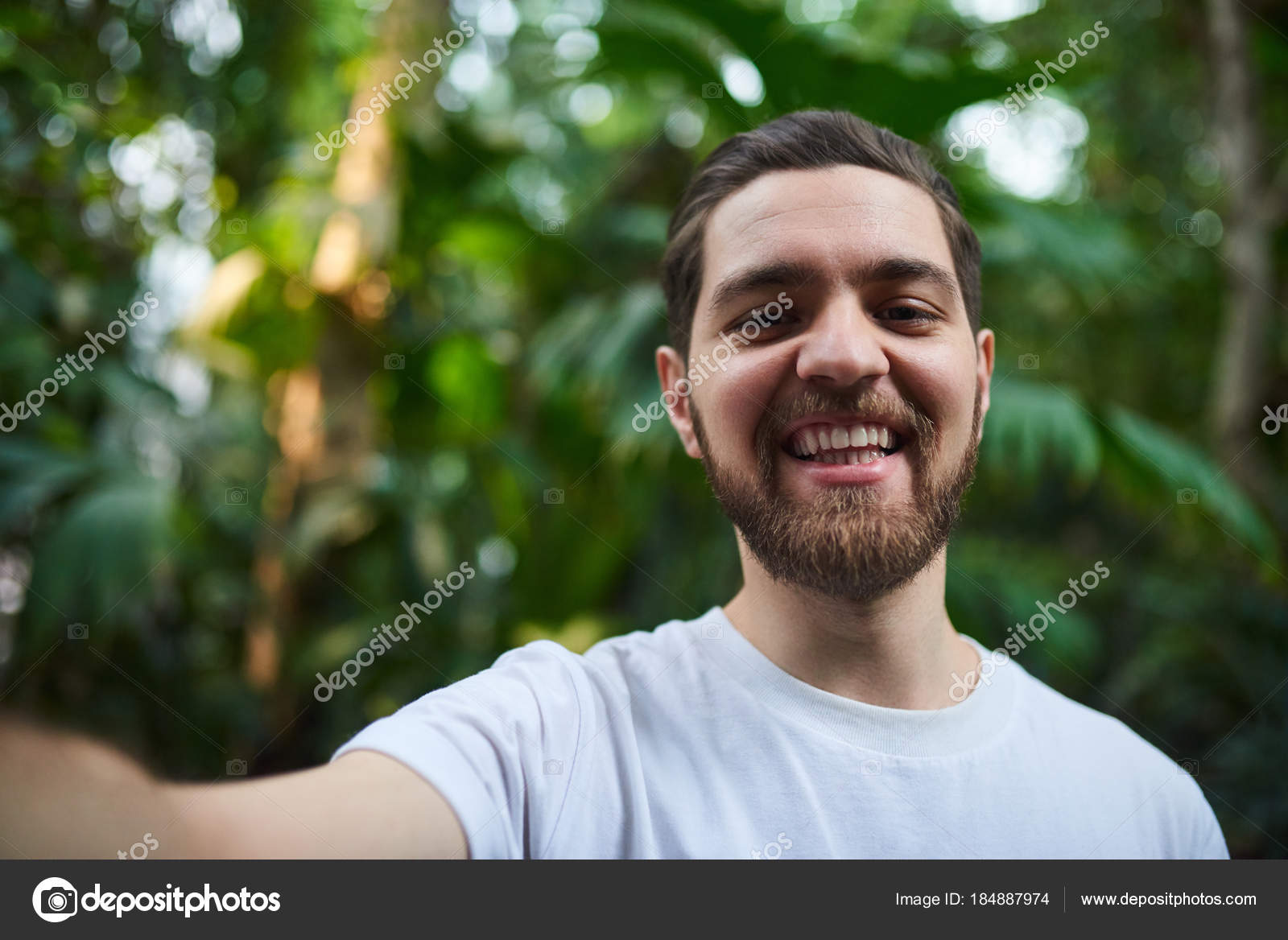 Closeup retrato de guapo elegante barbudo hombre de pie en el jardín  botánico f443fbd66ee