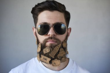 Handsome man in sunglasses with stickers on beard on gray background
