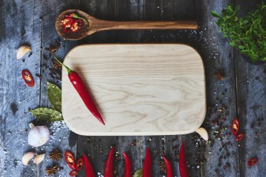 Top view of red chili peppers and cutting board on wooden surface background