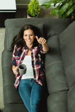 woman with cup on sofa