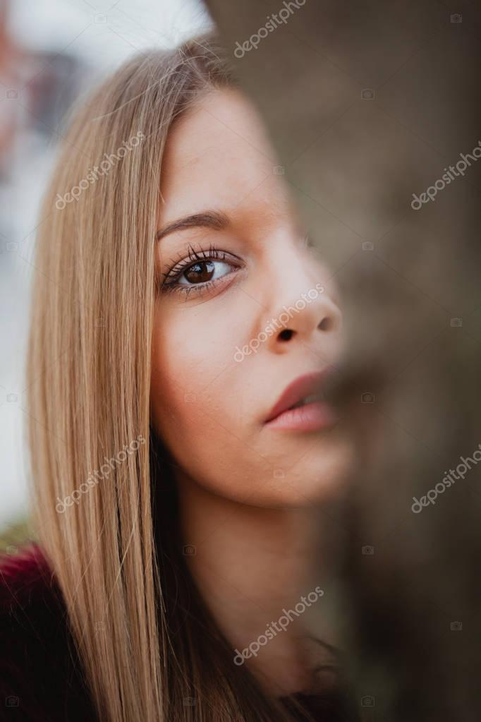 blonde girl next to tree trunk
