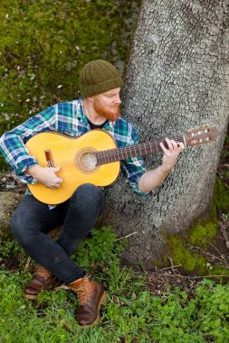 Handsome man with guitar in nature