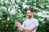 Casual guy in park taking selfie