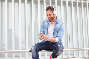 Casual man listening music outdoors