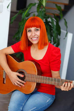 redhead happy young woman playing guitar at home