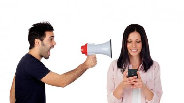 guy with megaphone shouting at girlfriend with mobile phone isolated on white background