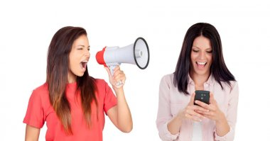 woman with megaphone shouting at her friend with mobile phone isolated on white background