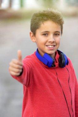 Child with dark hair listening music with blue headphones