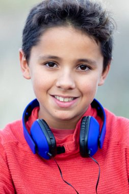 Child with dark hair listening music with blue headphones