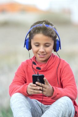 Child with dark hair listening music with blue hadphones and a m