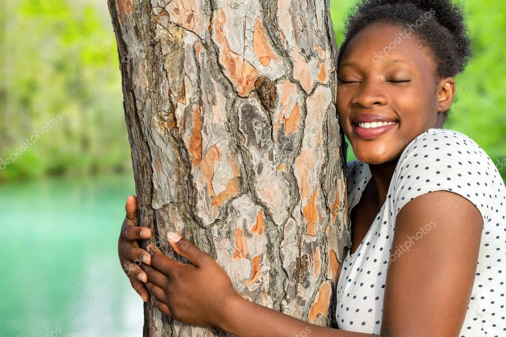 African girl embracing tree in wood