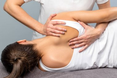 Detail of female therapist manipulating shoulder blade on patien