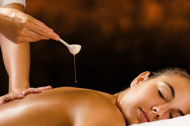 Therapist pouring oil on female back.