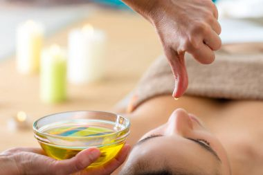 Macro close up of hand with oil drop above womans head in spa. Aromatic oil in glass bowl next to woman at Ayurvedic massage.