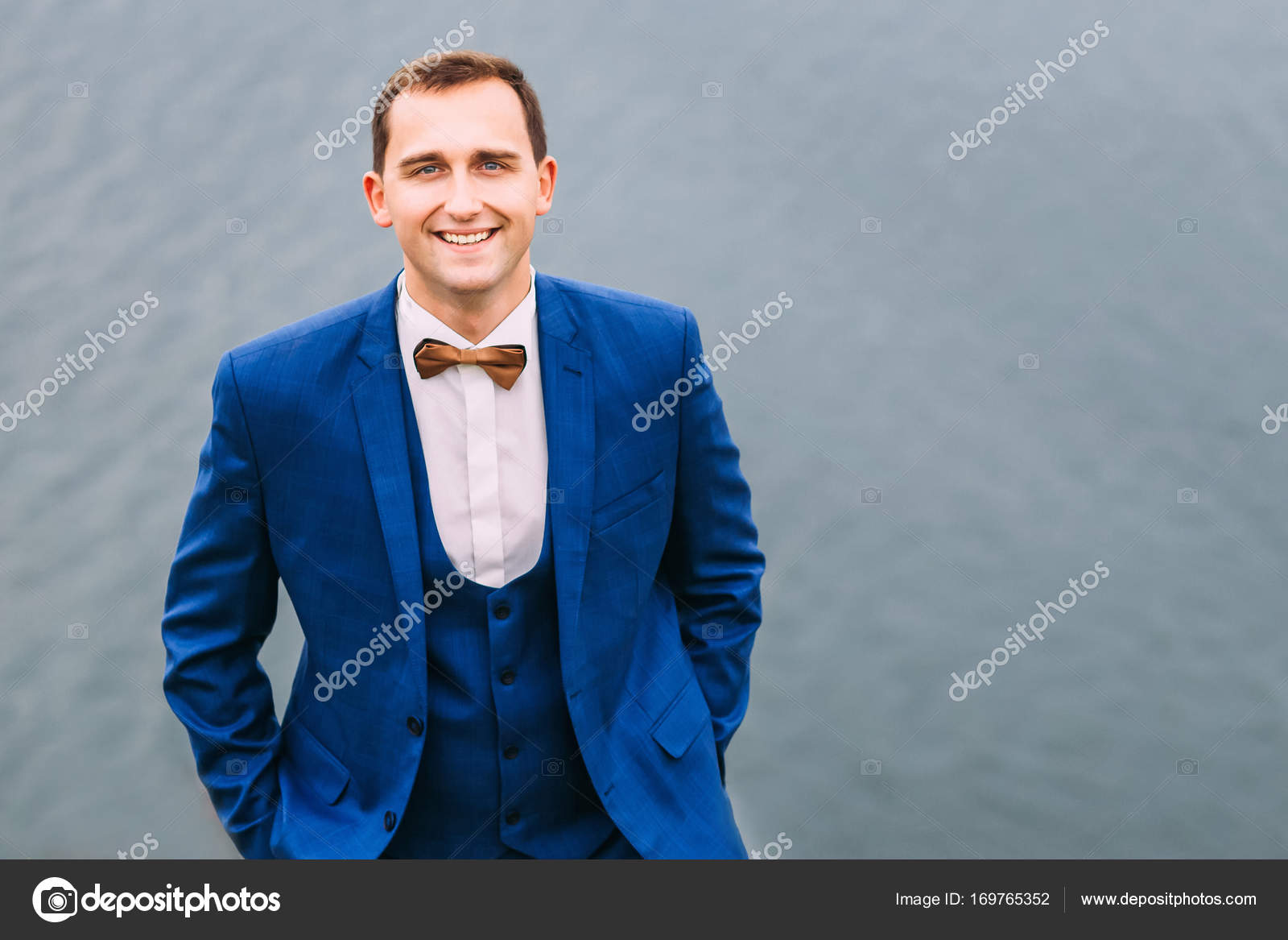 Stylish groom in blue suit, waistcoat and brown bow tie holding ...
