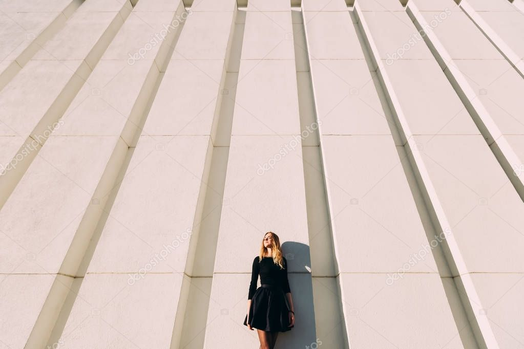 Urban picture of stylish girl near modern wall with vertical lines