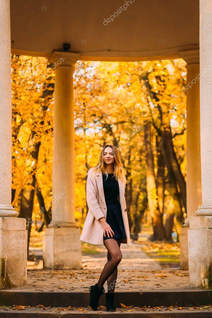 Beautiful woman posing for camera near columns in autumn orange park