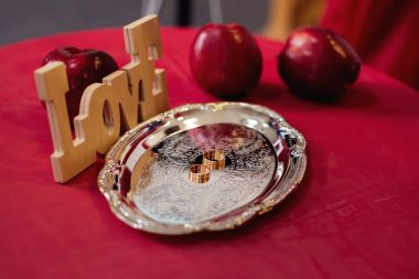 silver plate with wedding rings, placed on a table with a red cl