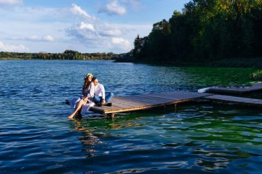 The woman and her husband are sitting at the pier of the lake an
