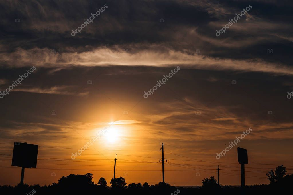 beautiful sunset and silhouettes of billboards and a pillar with