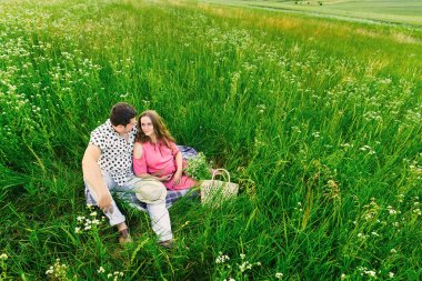 meadow with tall grass and the future parents sit on coverlet. b
