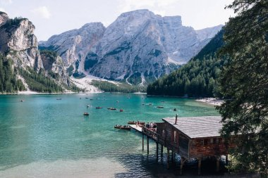 16 August 2019 - Lago di Braies, Italy - lake on background of mountains with typical wooden boats on the Lake Braies. stock vector