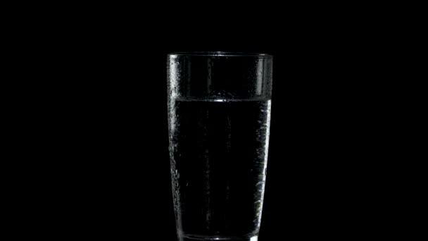 Sklenice vody s kapkami na vnější straně se otáčí ve tmě