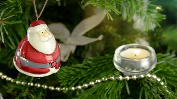 Christmas tree with Santa Claus decoration on it. Candle light  video effect.