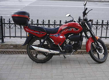 Motorcycle with a red tint and cool background .
