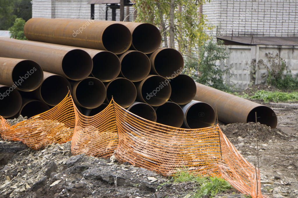Close-up of steel high-pressure pipes of various diameter bunch in warehouse