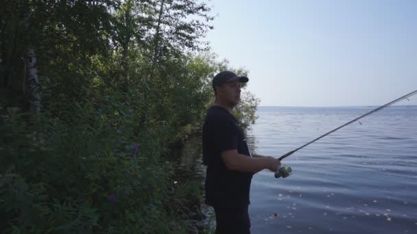 Halász egy horgászbot, a folyó partján. Halász ember fogások egy hal. Halászati