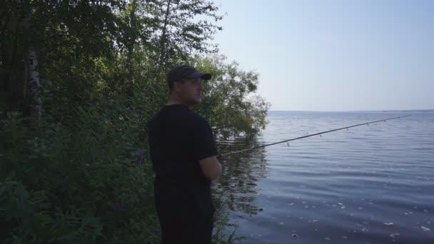 Horgászbottal a folyóparton. Halász ember fogások egy hal. Horgászat, spinning reel, a hal, a Breg folyók. -A koncepció egy vidéki kiruccanásra
