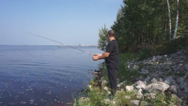 Muž rybář chytí rybu. Rybaření, spřádání naviják, ryby, řek Breg. -Pojem venkovské útočiště. Článek o rybaření.