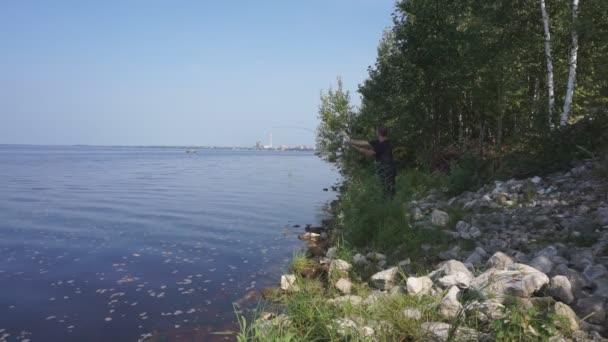 Horgászbottal a folyóparton. Halász ember fogások egy hal. Horgászat, spinning reel, a hal, a Breg folyók. -A koncepció egy vidéki kiruccanásra. Cikk a halászati.