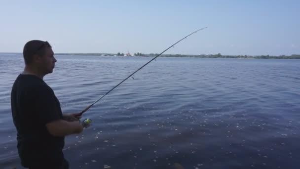 a folyó partján. Halász ember fogások egy hal. Horgászat, spinning reel, a hal, a Breg folyók. -A koncepció egy vidéki kiruccanásra. Cikk a halászati.